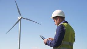 Posição do homem perto do moinho de vento e programa da utilização na tabuleta vídeos de arquivo