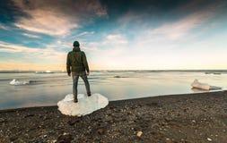 Posição do homem sobre um bloco de gelo imagem de stock