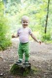 Posição do menino em um coto, orgulhoso de sua realização da aprendizagem andar as madeiras fotos de stock royalty free
