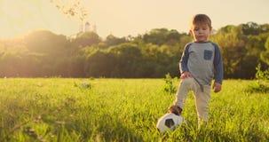 Posição do menino na grama com uma bola de futebol no por do sol vídeos de arquivo