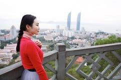Posição do turista da senhora em uma rocha na parte superior da montanha e para admirar a vista, Xiamen, China foto de stock