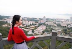 Posição do turista da senhora em uma rocha na parte superior da montanha e para admirar a vista, Xiamen, China fotos de stock