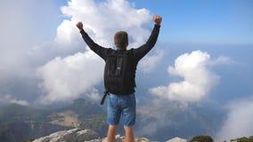 Posição do turista do menino no pico do monte e dos braços victoriously outstretching Indivíduo que aprecia a liberdade durante o filme
