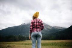Posição do viajante das mulheres para ver as montanhas das montanhas imagens de stock