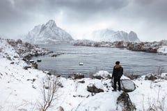 Posição do viajante do homem na rocha com opinião da vila de Reine no blizzard fotografia de stock royalty free