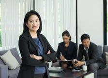 A posição e a cruz fêmeas do líder da mulher de negócios armam-se com a equipe dentro imagens de stock royalty free