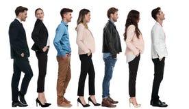 A posição elegante do homem na linha de outros povos olha acima foto de stock royalty free