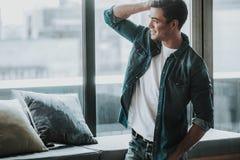 Posição emocional do homem perto da janela e toque de seu cabelo imagens de stock royalty free