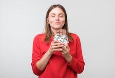 Posição europeia da jovem senhora sobre o fundo branco ao morder o chocolate fotografia de stock