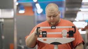 Posi??o excesso de peso nova do homem no gym na escala mec?nica vídeos de arquivo