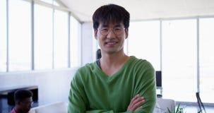 Posição executiva masculina asiática considerável com os braços cruzados no escritório moderno 4k filme