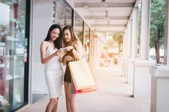 Posição fêmea asiática bonita de dois amigos e para apreciar a compra com saco de papel da terra arrendada imagens de stock royalty free