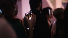 Posição fêmea atrativa nova de volta à câmera e mantimento de um vidro do vinho branco no partido e observação no filme