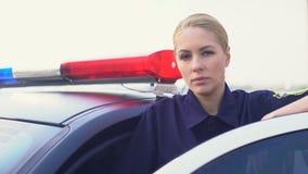 Posição fêmea concentrada da situação da estrada da monitoração do oficial perto do carro de polícia filme