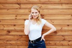 Posição fêmea de riso atrativa com telefone celular contra o fundo de madeira da parede foto de stock