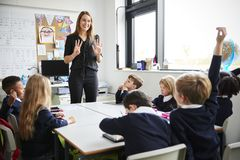 Posição fêmea em uma sala de aula que gesticula aos alunos que sentam-se em uma tabela que escuta, um levantamento do professor d fotografia de stock royalty free