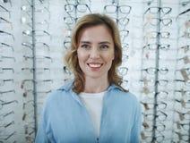 Posição fêmea feliz na loja dos vidros imagens de stock royalty free