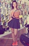 Posição fêmea na loja ostentando dos bens com bolas e raquete Fotos de Stock Royalty Free