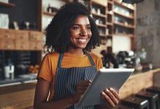 Posição fêmea nova do proprietário no café que guarda a tabuleta digital fotografia de stock royalty free
