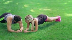 Posição feliz do homem e da mulher na prancha na grama verde no treinamento da aptidão exterior vídeos de arquivo