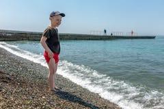 Posição feliz do menino na frente do mar em uma praia fotografia de stock