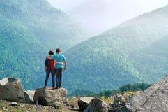Posição feliz dos pares abraçada na borda do penhasco e em apreciar a opinião bonita da manhã nas montanhas Fotografia de Stock Royalty Free