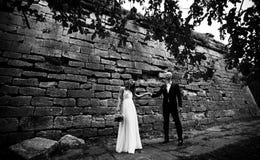 Posição lindo do olhar dos noivos atrás de uma parede velha da A.A. Imagens de Stock