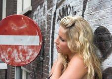Posição loura atrativa ao lado de um sinal de estrada vermelho Imagem de Stock