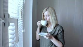Posição loura bonita thinkful triste nova da mulher perto da janela com as cortinas na manhã e no café bebendo video estoque