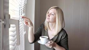 Posição loura bonita thinkful triste nova da mulher perto da janela com as cortinas na manhã e no café bebendo vídeos de arquivo