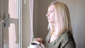 Posição loura bonita thinkful triste nova da mulher perto da janela na manhã, café bebendo e cortinas do levantamento vídeos de arquivo