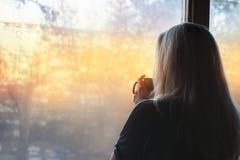 Posição loura da mulher pela janela, com o copo de café nas mãos fotos de stock royalty free