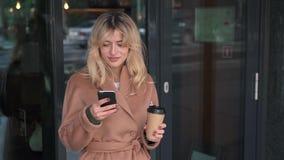 Posição loura da mulher perto do café e utilização de seu smartphone filme