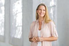 Posição madura de sorriso da mulher fotografia de stock