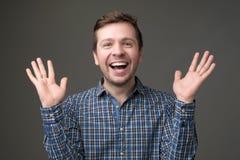 Posição madura entusiasmado do homem com mãos levantadas e vista da câmera imagem de stock