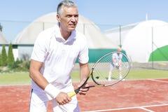 A posição madura segura do homem com a raquete de tênis contra o amigo que joga dobros combina na corte foto de stock royalty free