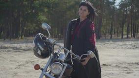Posição moreno caucasiano nova bonita da menina na motocicleta que olha afastado na frente do passatempo da floresta do pinho, vi filme