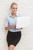 Posição nova da mulher de negócios e sorriso ao guardar o portátil fotografia de stock royalty free