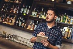 Posição nova do barman no contador da barra que verifica o inventário imagens de stock