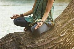 Posição praticando da ioga dos lótus da jovem mulher ao lado do rio fotos de stock royalty free