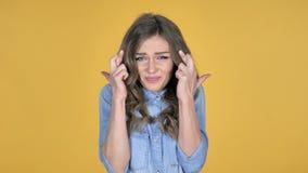 Posição preocupada da moça com o dedo cruzado para a boa sorte no fundo amarelo vídeos de arquivo