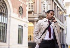 Posição preta milenar em uma rua em Londres que fala em seu telefone, baixo ângulo do homem de negócios foto de stock