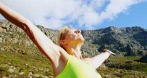 Posição superior da mulher com os braços excedidos no campo 4k video estoque