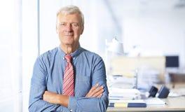 Posição superior do homem de negócios com os braços cruzados no escritório foto de stock royalty free