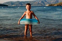 Posição velha de cinco anos bonito do menino com círculo inflável de borracha no mar em Turquia fotografia de stock royalty free