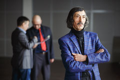 Posição vestindo envelhecida velha do casaco azul do homem de negócios imagens de stock