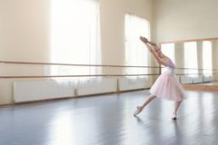 Posições de bailado praticando da bailarina pequena na classe clara fotos de stock royalty free