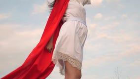 posi??o bonita em um campo em um casaco vermelho, casaco da menina do super-her?i que vibra no vento sonhos da menina de tornar-s filme