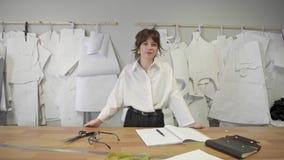 Posi??o de sorriso do desenhador de moda f?mea no fundo dos testes padr?es de papel vídeos de arquivo