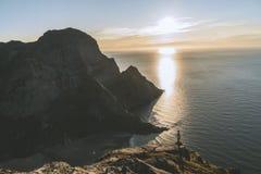 Posi??o do alpinista do homem na rocha da montanha m?xima no por do sol Montanha de Ryten, Noruega imagens de stock